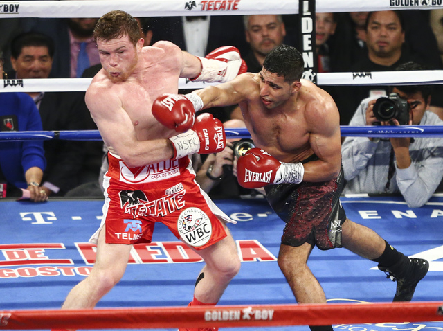 Canelo Alvarez, left, takes a hit from Amir Khan during their the WBC middleweight championship fight at T-Mobile Arena in Las Vegas on Saturday, May 7, 2016. Alvarez won with a knockout in the 6t ...