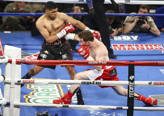 Canelo Alvarez, right, lands a punch against Amir Khan during their the WBC middleweight championship fight at T-Mobile Arena in Las Vegas on Saturday, May 7, 2016. Alvarez won with a knockout in  ...