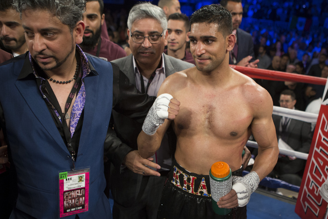 "Amir Khan raises his arm after losing by knockout in the sixth round against Saul ""Canelo"" Alvarez in the WBC Middleweight Title bout at the T-Mobile Arena on Saturday, May 7, 2016, in Las Veg ..."