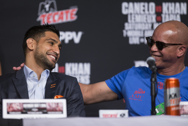 Amir Khan, left, speaks with his boxing trainer Virgil Hunter during the final press conference before Khan's fight at the Ka Theater inside MGM Grand casino-hotel on Wednesday, May 4, 2016, in La ...