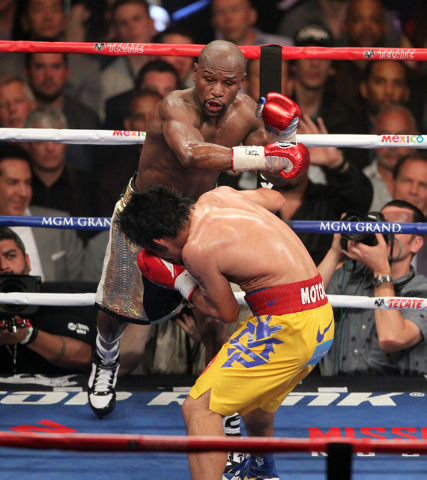 Floyd Mayweather Jr., top, goes after Manny Pacquiao in the sixth round of their welterweight unification boxing match at the MGM Grand Garden Arena in Las Vegas on Saturday, May 2, 2015. (Erik Ve ...