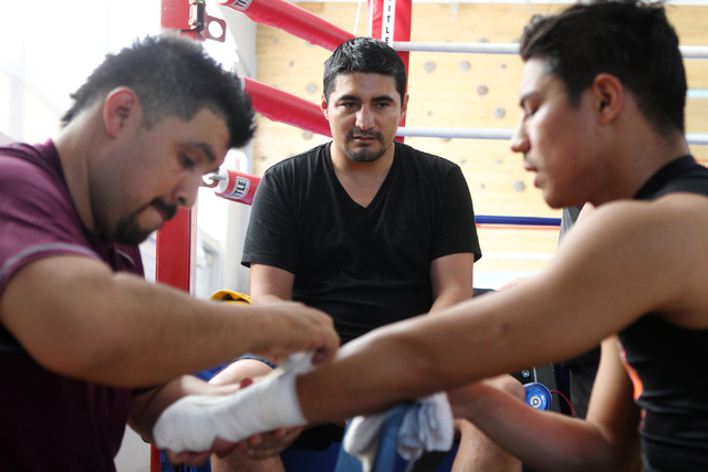 Boxing trainer and retired professional boxer Erik Morales, center, looks on as his boxer Jesse Vargas, right, gets his hands wrapped for a sparring practice at the Spring Mountain Youth Camp gym  ...