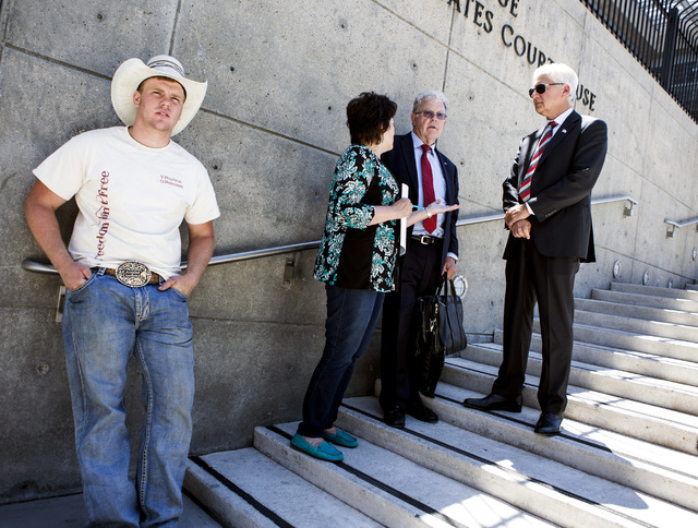 Art Bundy, left, son of Nevada rancher Cliven Bundy, stands while his mother Carol Bundy talk to attorneys  Joel Hansen and Larry Klaymam, right, in front of Lloyd George U.S. Courthouse on Tuesda ...