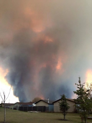 Fire burns and smoke fills the air near homes in Fort McMurray, Alberta, on Tuesday May 3, 2016. The entire population of the Canadian oil sands city of Fort McMurray, has been ordered to evacuate ...