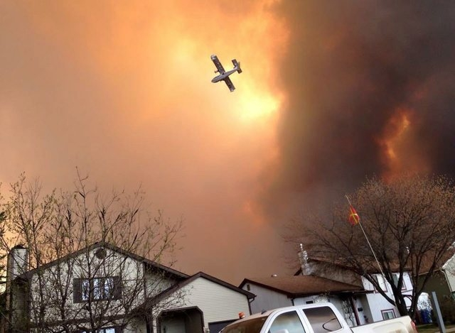 Smoke fills the air as a small plane flies overhead in Fort McMurray, Alberta, Tuesday, May 3, 2016. The entire population of the Canadian oil sands city of Fort McMurray, has been ordered to evac ...