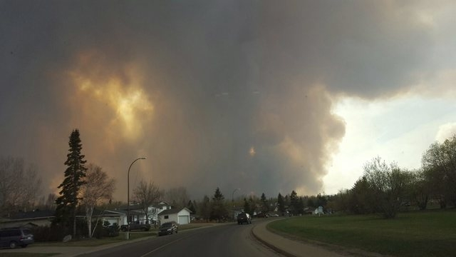 Smoke rises from a wildfire outside of Fort McMurray, Alberta, Tuesday, May 3, 2016. The entire population of the Canadian oil sands city of Fort McMurray, has been ordered to evacuate as a wildfi ...