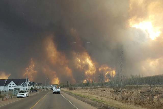 This photo take through a car windshield shows smoke rising from a wildfire rages outside of Fort McMurray, Alberta, Tuesday, May 3, 2016. The entire population of the Canadian oil sands city of F ...