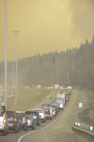 Smoke fills the air as people drive on a road in Fort McMurray, Alberta, Tuesday, May 3, 2016. At least half of a northern Alberta city was ordered evacuated Tuesday as a wildfire whipped by winds ...