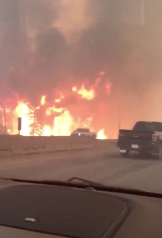 This photo provided by Tyler Burgett shows flames from a wildfire along Highway 63 in Fort McMurray, Alberta, Tuesday, May 3, 2016. At least half of the northern Alberta city was ordered evacuated ...