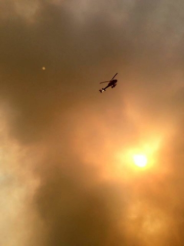 Smoke fills the air as a helicopter flies overhead in Fort McMurray, Alberta on Tuesday, May 3, 2016. The entire population of the Canadian oil sands city of Fort McMurray, has been ordered to eva ...