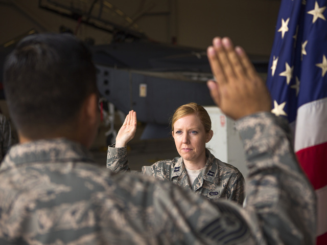 Capt. Madison Gilbert, officer in charge at the 757th Aircraft Maintenance Squadron, re-enlists Tech Sgt. Darren Garcia during a ceremony at Nellis Air Force Base on Wednesday, April 27, 2016.  (J ...