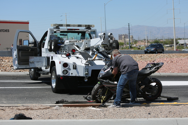 A worker prepares a motorcycle to be towed on Stephanie Street, where a rider died after leaving the roadway and striking a pole on Friday, May 13, 2016 in Las Vegas. Brett Le Blanc/Las Vegas Revi ...