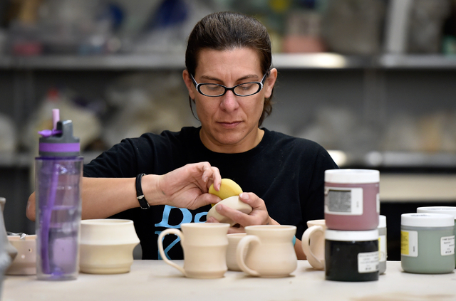 """Constance Stotzer, at work at Clay Arts Vegas, collaborated on """"We Are the People in Your Neighborhood,"""" featured in the """"Vegas to a Local"""" ceramics exhibit at  ..."""