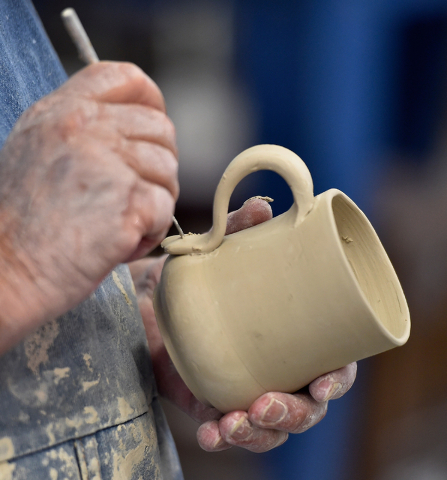 """Brian Ayriss secures a handle to a ceramic mug he made at the Clay Arts Vegas studio; he's represented in Clay Arts' current """"Vegas to a Local"""" exhibit at City Hall. David Becker ..."""