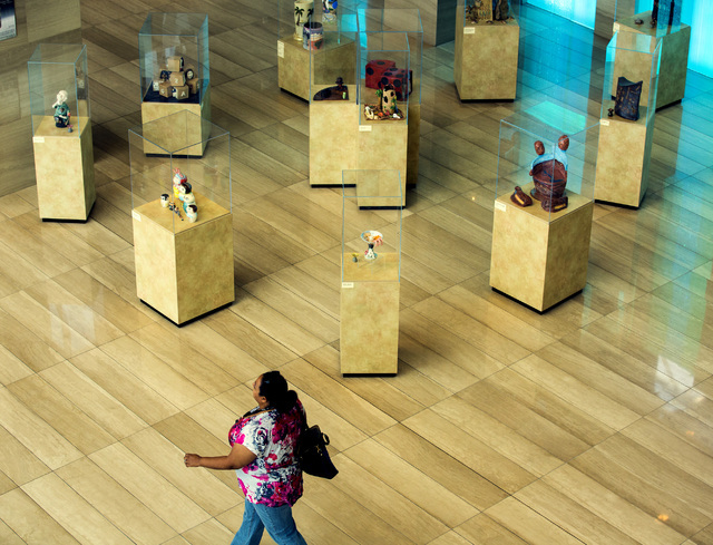 """A woman walks by the """"Vegas to a Local"""" exhibit -- created by Clay Arts Vegas artists -- in the first-floor Grand Gallery at Las Vegas City Hall. Jeff Scheid/Las Vegas Review-Journal Follow @jlscheid"""