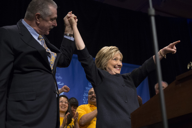 """Anthony """"Marc"""" Perrone, left, international president at United Food and Commercial Workers International Union,  raises hands with Democratic presidential candidate Hillary Clinton  ..."""