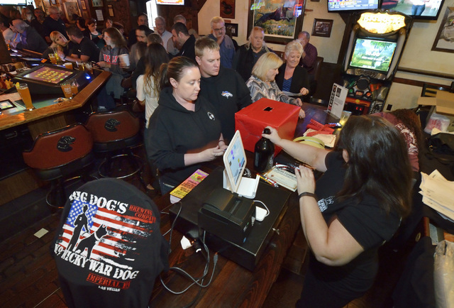 Ashley Smith, left, and Josh Padilla buy merchandise from cashier Sharon Apple during a launch for K-9 Nicky War Dog Imperial IPA and a benefit in honor of Nicky, a K-9 officer killed in the line  ...