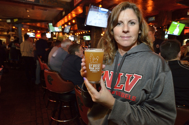 Lisa Van Syckle is shown with a glass of K-9 Nicky War Dog Imperial IPA during a launch for the beer and a benefit in honor of Nicky, a K-9 officer killed in the line of duty. The event was held a ...