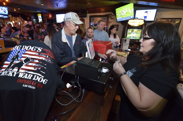 Terry Ostlund, left, buys merchandise from cashier Sharon Apple during a launch for K-9 Nicky War Dog Imperial IPA and a benefit in honor of Nicky, a K-9 officer killed in the line of duty. The ev ...
