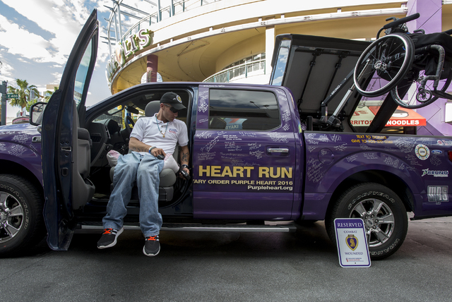Marine Cpl. Tyler Huffman gets into a Ford F150 adapted to be driven by combat-wounded veterans on May 13, 2016, on Fremont Street in Las Vegas. Huffman suffered an injury in combat that left him  ...