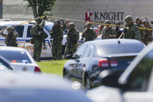 Sheriff's deputies exit Knight Transportation after an employee, who was recently fired, returned to the business and fatally shot an employee before killing himself, Wednesday, May 4, 2016, in Ka ...