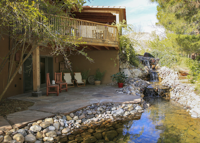 Behind the house is a tall tiered river rock waterfall that descends into a fish pond, and gradually trickles into a wash. (ELKE COTE/MILLIONS)