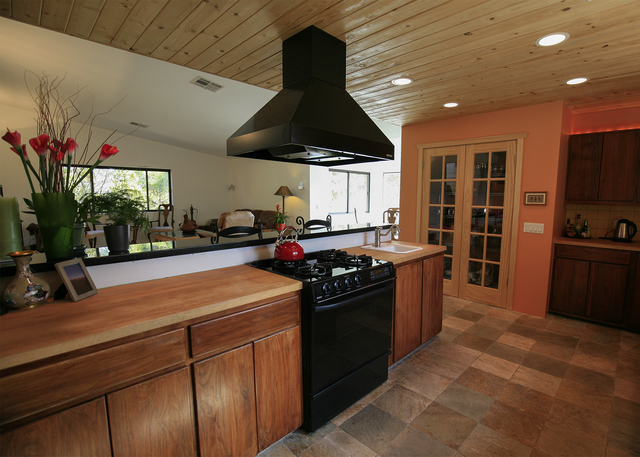 The kitchen has solid walnut cabinets. Its ceiling is made of knotty pine, and it has an eating nook looking east over the orchard. (ELKE COTE/MILLIONS)