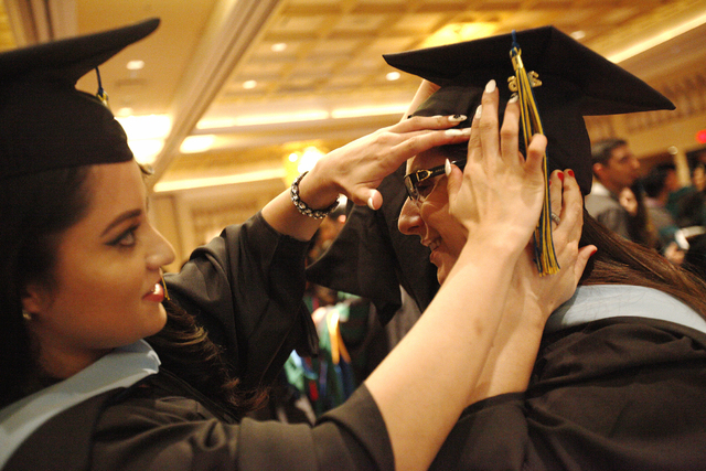 Touro University Nevada graduate Yischelli Martinez adjusts the cap of fellow graduate Maggie Marschner as they wait in a ballroom for their graduation ceremony at the Rio Hotel and Casino Sunday, ...