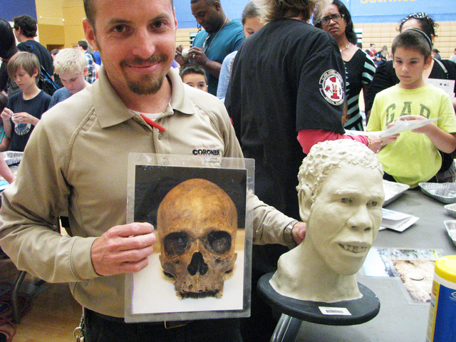 Scott Lautzenheiser, a coroner investigator for Clark County, shows a photo of a skull and the facial reconstruction based on that skull at the Crimebusters! event May 2, 2016, at the Veterans Tri ...