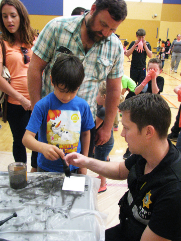 Elias Scholten applies black powder to a fingerprint while his father Mathew looks on at the Crimebusters! event May 2, 2016, at the Veterans Tribute Career Technical Academy, 2531 Vegas Drive. F. ...