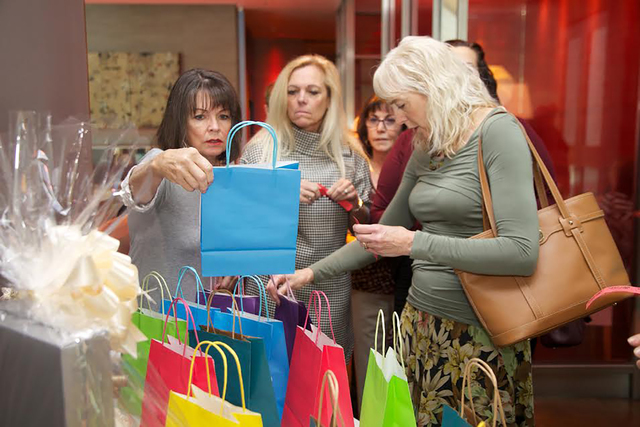 Attendees check out the raffle prize bags at the Dare to Dream Fashion Show fundraiser April 30, 2016, at Neiman Marcus on theStrip. The event supported the Women's Club of Summerlin Dare t ...