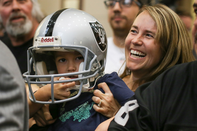 Cheri Branca, of Las Vegas, holds up her four-year-old Levi Branca up while meeting Mark Davis during a Southern Nevada Tourism Infrastructure Committee meeting at UNLV in Las Vegas on Thursday, A ...