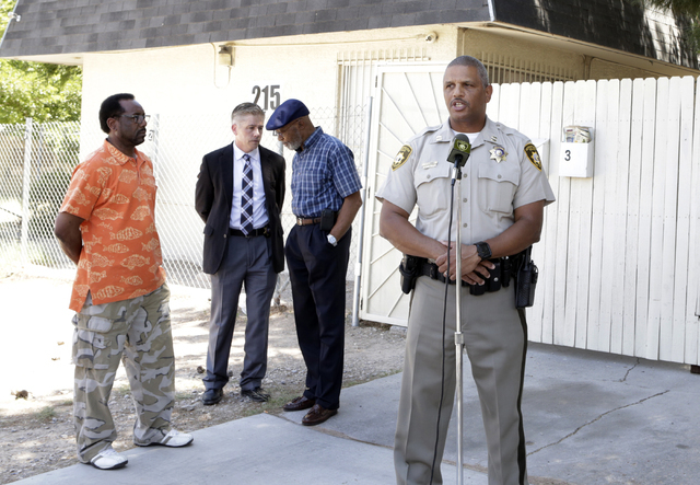 Las Vegas police Capt. Robert Plummer speaks about an arrest made in a triple homicide, as he briefs the media as Metro Lt. Dan McGrath, second left, talks to community organizers on Tuesday, May  ...