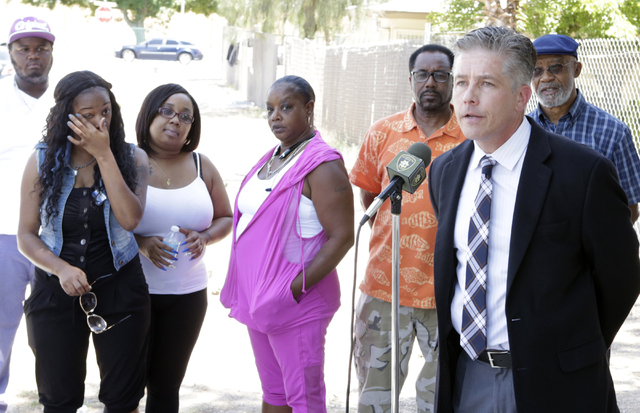 Veronica Gaston, left, and Latoya Carroll, second left, sisters of murder victim Lashunda Carroll, and Morty Cornell Young, listen as Metro Lt. Dan McGrath speaks about an arrest made in a triple  ...