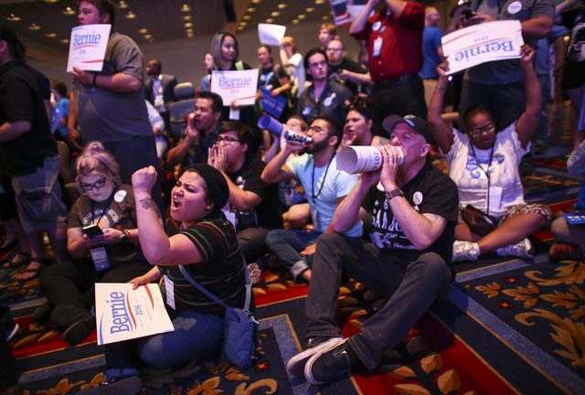 Supporters of Democratic presidential candidate Bernie Sanders, including Valeria Romano, center left, and Johnny Hancen, center right, gather in the front of the room during the Nevada State Demo ...