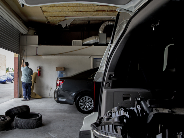 Jose Tinoco lowers the door to his garage after being cited by the Nevada Department of Motor Vehicles for operating an auto body shop without a license, Tuesday, May 17, 2016, in Las Vegas. Benja ...
