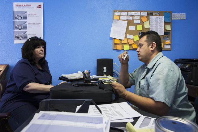 Linda Vantilborg, left, a compliance investigator with the Nevada Department of Motor Vehicles, issues a citation to Jose Tinoco for operating an auto body shop without a license, Tuesday, May 17, ...