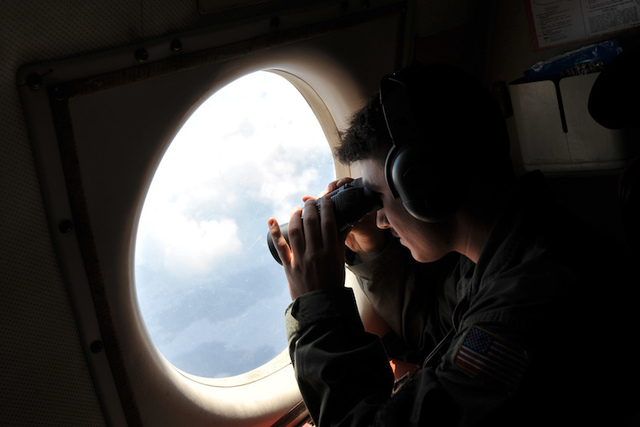 U.S. Navy LT. JG Dylon Porlas uses binoculars to look through the window of a U.S. Navy Lockheed P-3C Orion patrol aircraft from Sigonella, Sicily, Sunday, May 22, 2016, searching the area in the  ...