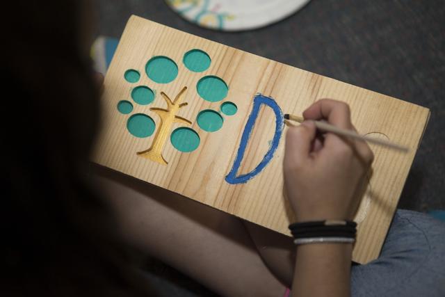Ayleen Kotis, 9, paints a wood carving sign at Discovery Charter School April 27, 2016, in Las Vegas. Erik Verduzco/View