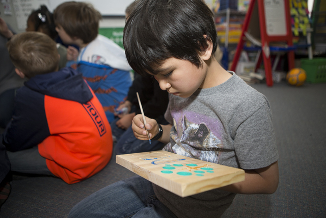 Kent Eisma, 7, paints a wood carving sign at Discovery Charter School April 27, 2016, in Las Vegas. A company that makes automated 3-D carving machines donated machines to a school in each of the  ...
