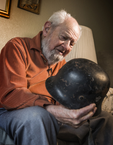 Las Vegan Vince Shank, 99, holds a German WWII soldiers helmet during an interview Thursday, March 3, 2016 at a senior living center. He was a bugler in Stalag III and went on to make a career pla ...