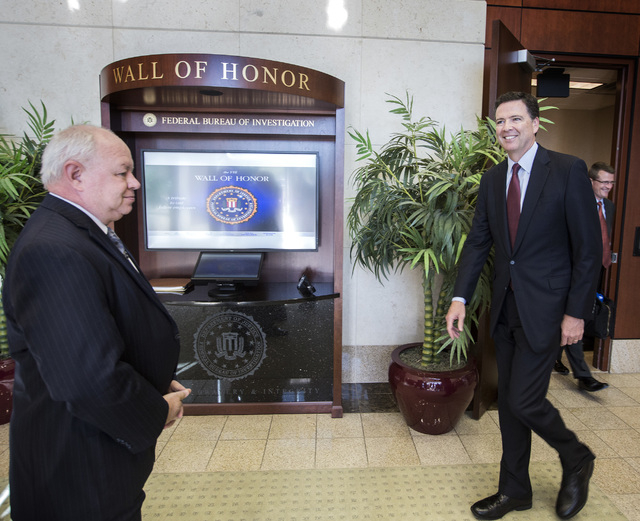 FBI Director James B. Comey, right, arrives for a press conference at FBI headquarters, 1787 W. Lake Mead Boulevard onTuesday, Sept. 9, 2014. He discussed the war on terrorism but would not talk a ...