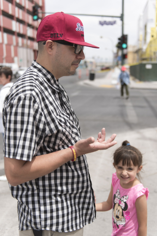 Roberto Mendoza stands with his 4-year-old daughter, Kaydence, as he speaks with a reporter about how he could cope with a surprise $1,000 bill near 7th Street and Fremont Street in downtown Las V ...