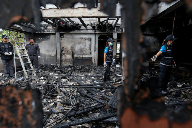 Forensic exports inspect a burnt building at the Pitakkiat Wittaya School in the northern province of Chiang Rai, Thailand, May 23, 2016. (Athit Perawongmetha/Reuters)
