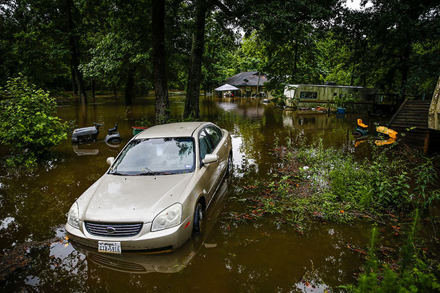 A car and home sit in flood water from Spring Creek along North Ravenswood Drive, Friday, May 27, 2016, in Magnolia, Texas. (Michael Ciaglo/Houston Chronicle via AP)
