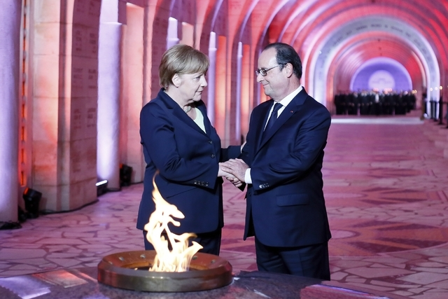 French President Francois Hollande, right, and German Chancellor Angela Merkel pay their respect in front of the Eternal Flame at the Douaumont's Ossuary, in Douaumont, northeastern France, Sunday ...