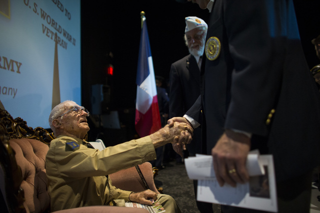 People greet World War II veteran Tech. Sgt. Elmer J. Hess, 98, before he receives the French Legion of Honor medal at Wayne Newton's Casa de Shenandoah Visitor Center in LAs Vegas on Wednesday, A ...