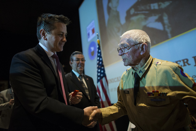 Honorary Consul for Southern Nevada Eric Auger, left, presents World War II veteran Tech. Sgt. Elmer J. Hess, 98, with the French Legion of Honor medal at Wayne Newton's Casa de Shenandoah Visitor ...