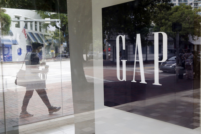 A pedestrian walks past a Gap store in Miami. The Gap Inc. reports earnings on Thursday, May 19, 2016. (Lynne Sladky/AP)