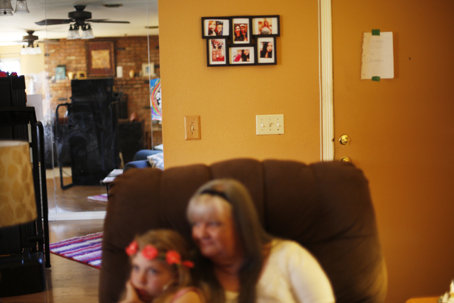 Kairi and her grandmother Cherlyn Branton sit together where a picture frame shows photos of their family in Branton's home in Las Vegas Sunday, May 1, 2016. (Rachel Aston/Las Vegas Review-Journal ...